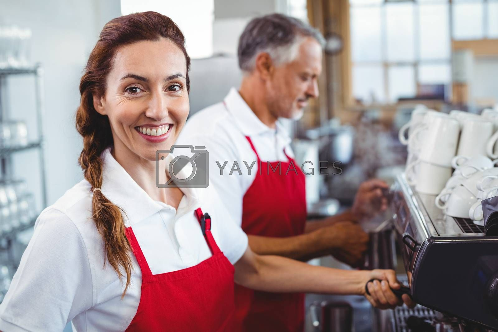 Royalty free image of Smiling barista using the coffee machine with colleague behind by Wavebreakmedia