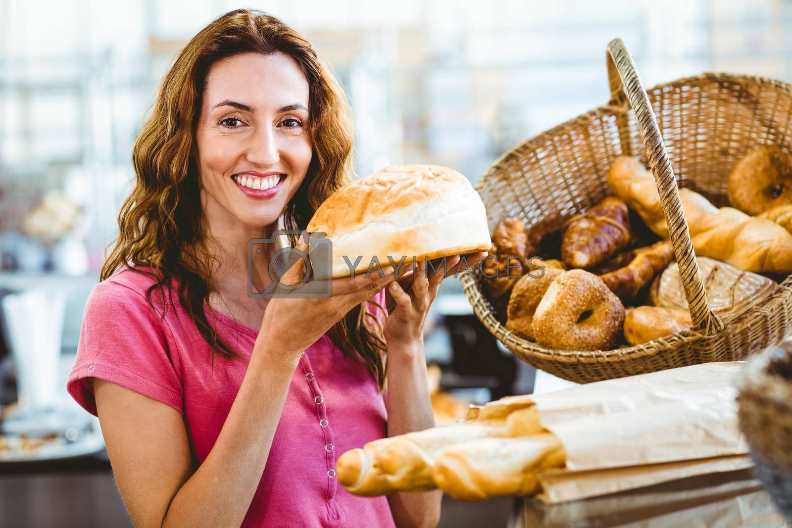 Royalty free image of Pretty brunette showing loaf of bread by Wavebreakmedia