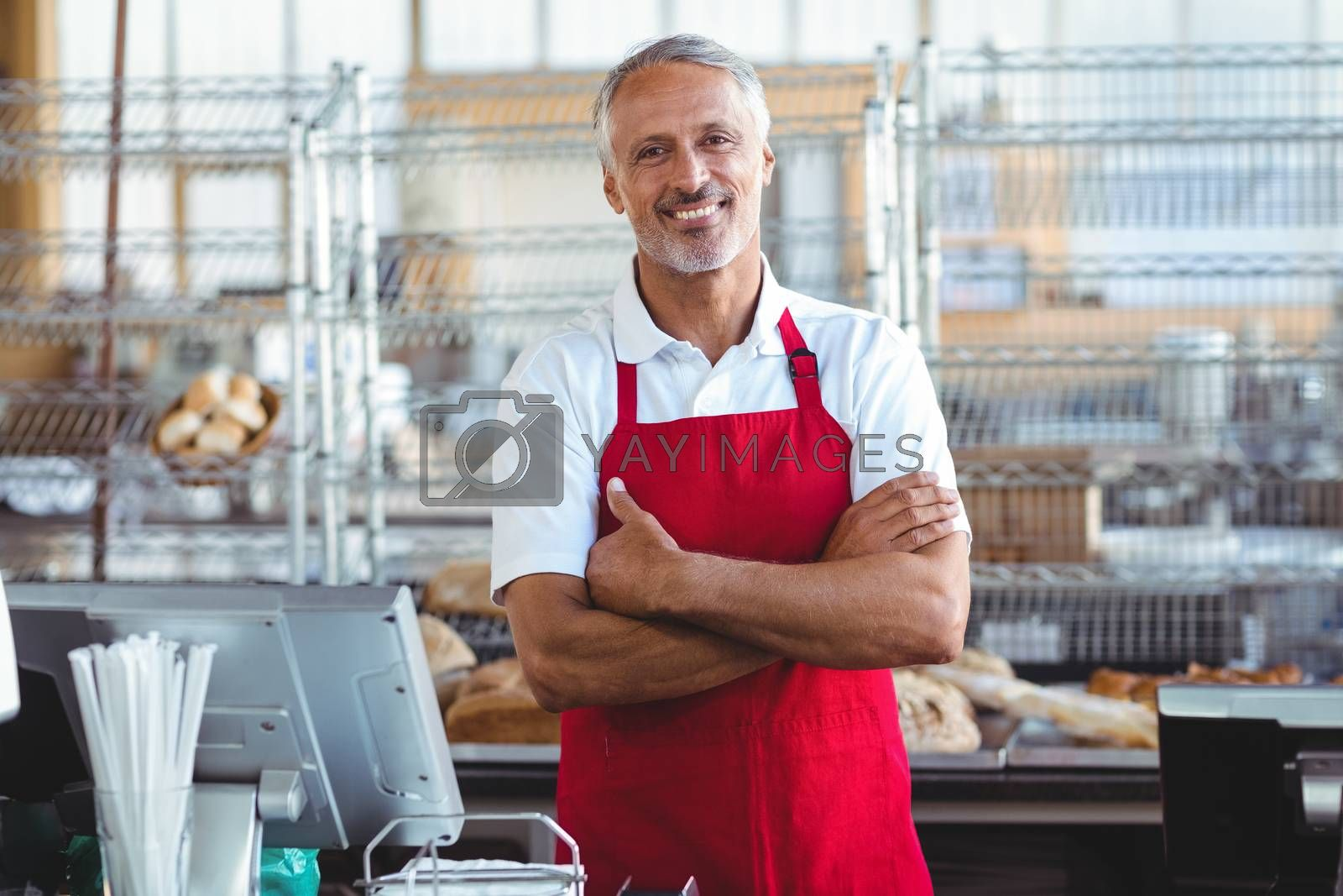 Royalty free image of Barista smiling at camera with arms crossed by Wavebreakmedia