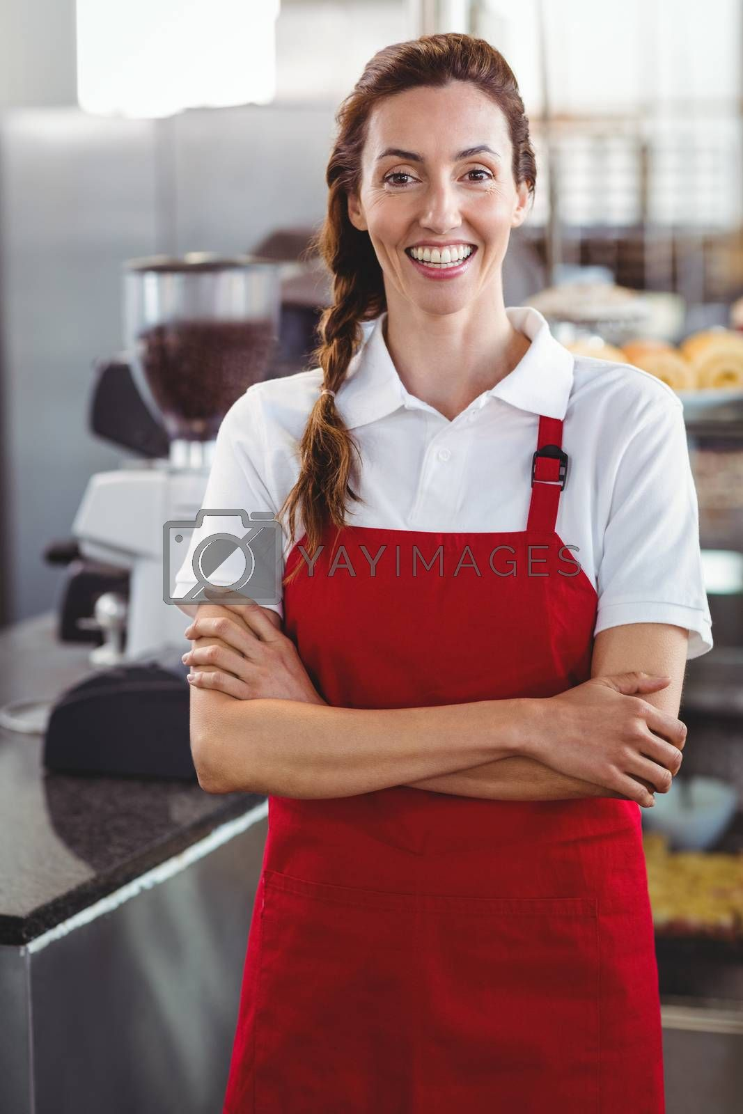 Royalty free image of Pretty barista smiling at camera with arms crossed by Wavebreakmedia