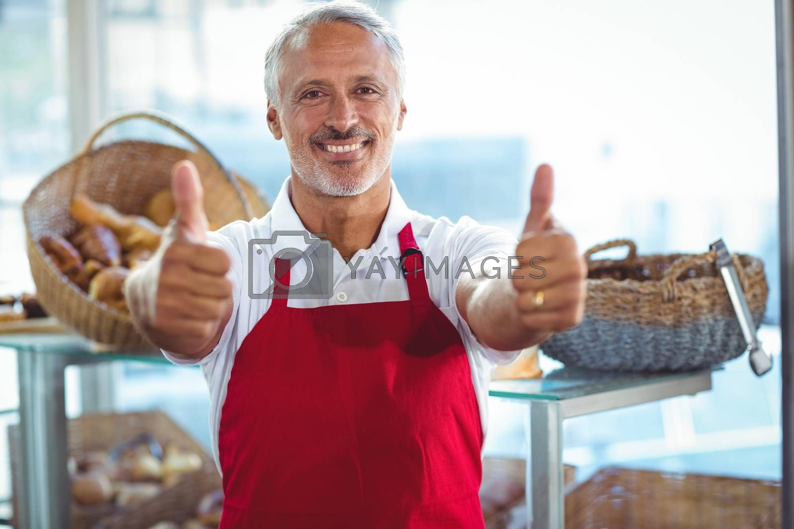 Royalty free image of Barista gesturing thumbs up and smiling at camera  by Wavebreakmedia