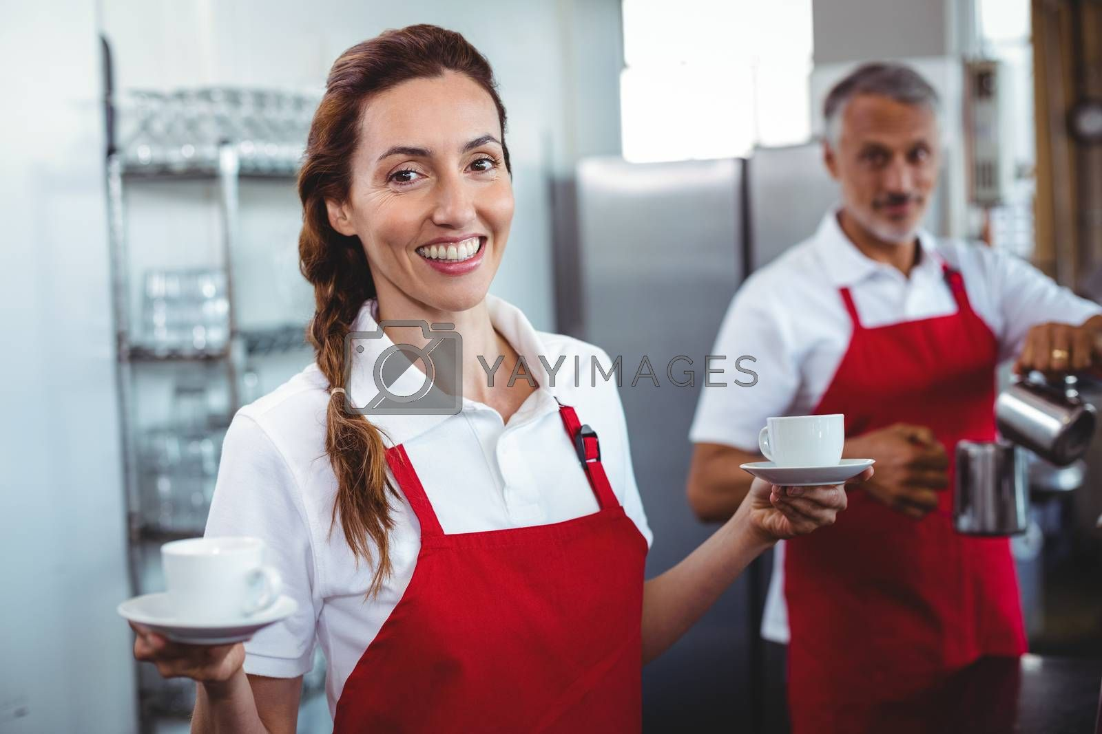 Royalty free image of Pretty barista holding cups of coffee with colleague behind by Wavebreakmedia