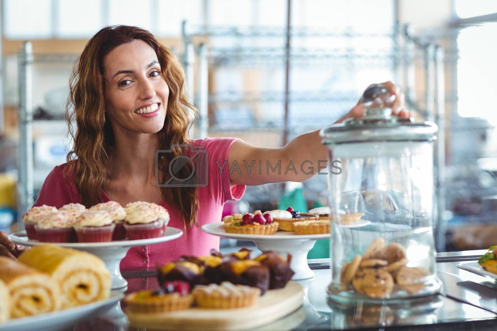 Royalty free image of Pretty brunette smiling at camera behind plates of pastries by Wavebreakmedia