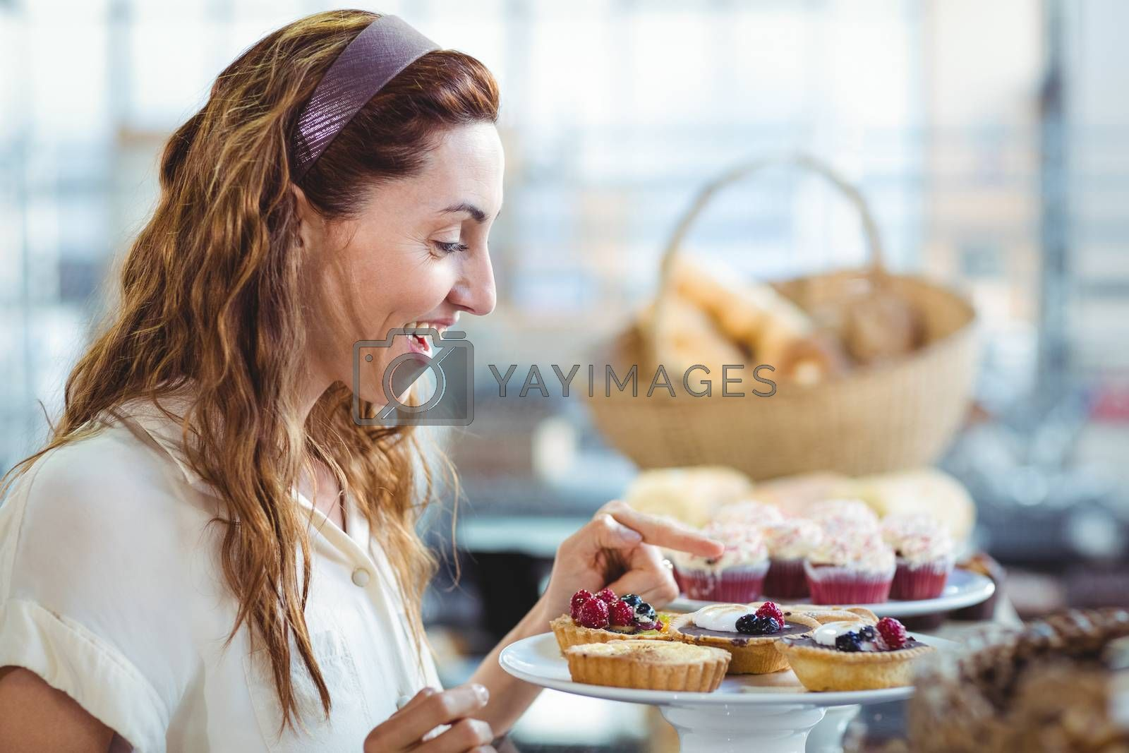 Royalty free image of Astonished pretty woman pointing at cakes by Wavebreakmedia