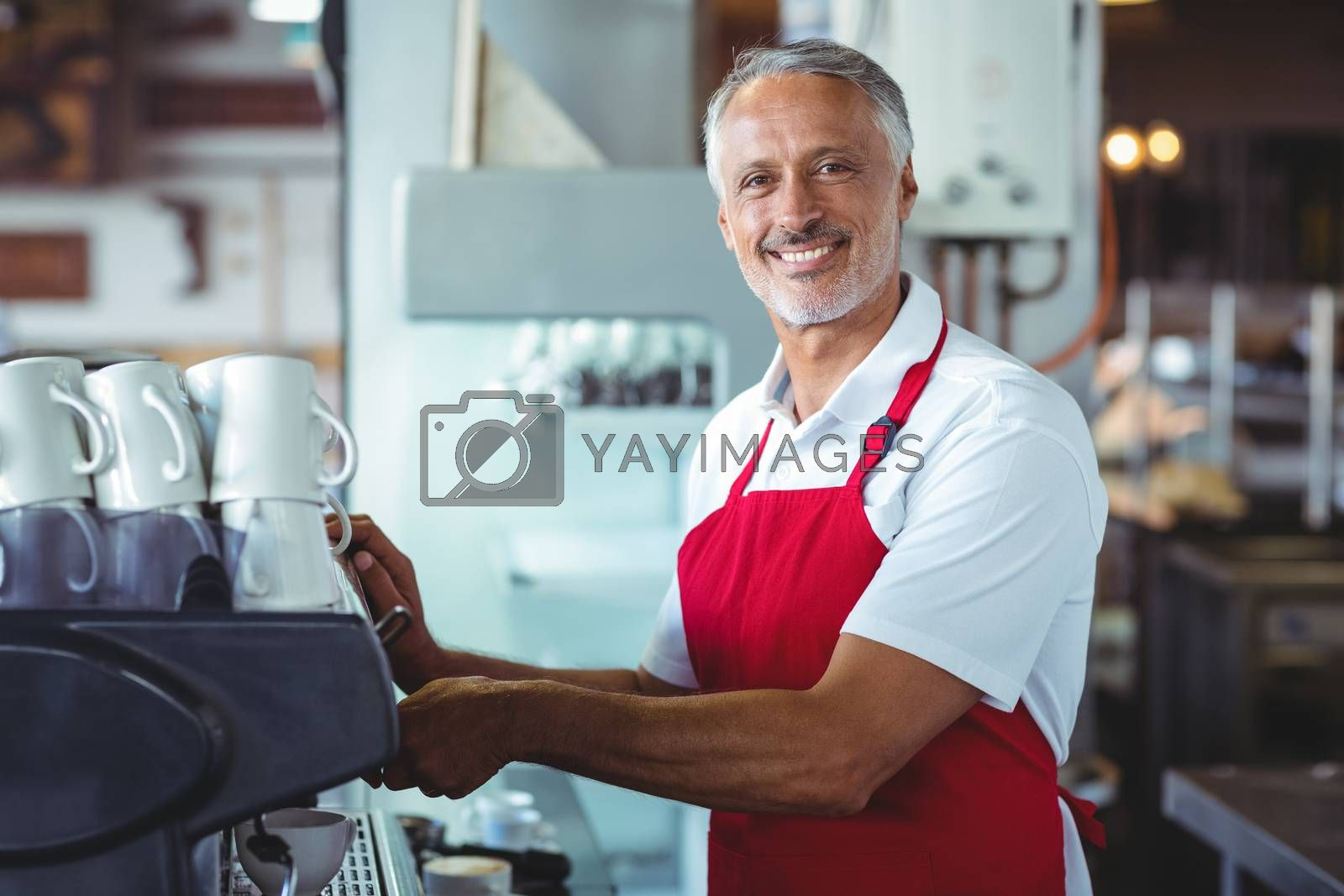 Royalty free image of Happy barista smiling at camera and using the coffee machine by Wavebreakmedia