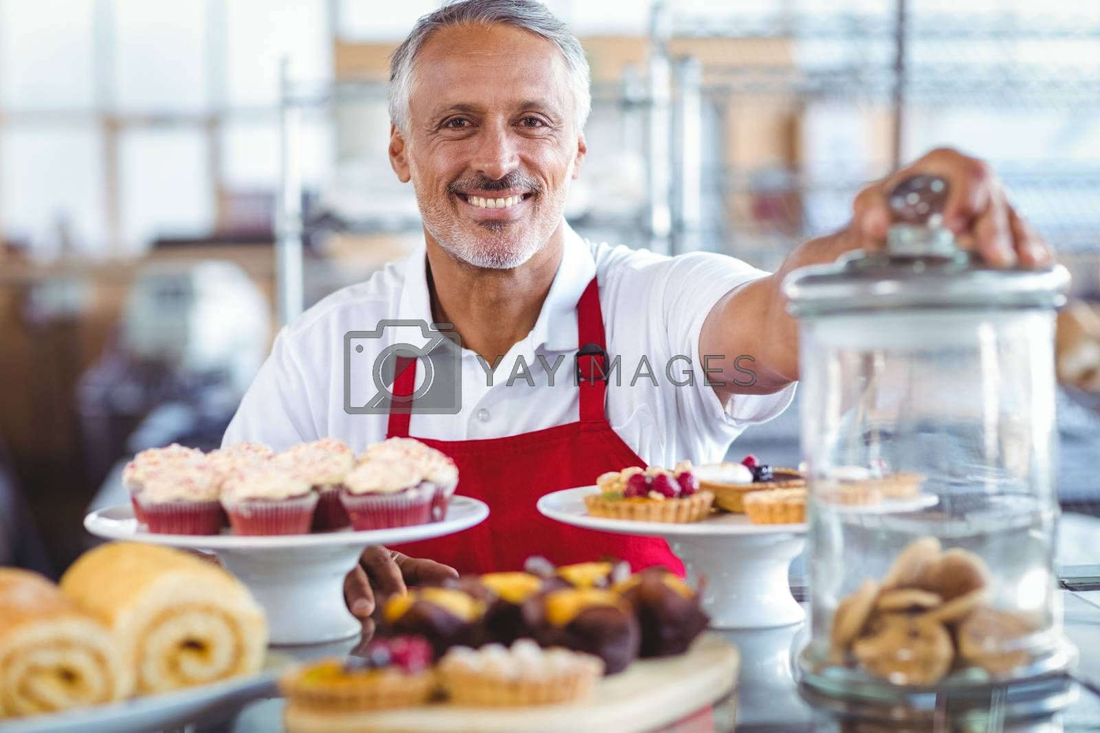 Royalty free image of Happy barista smiling at camera behind plates of cakes by Wavebreakmedia