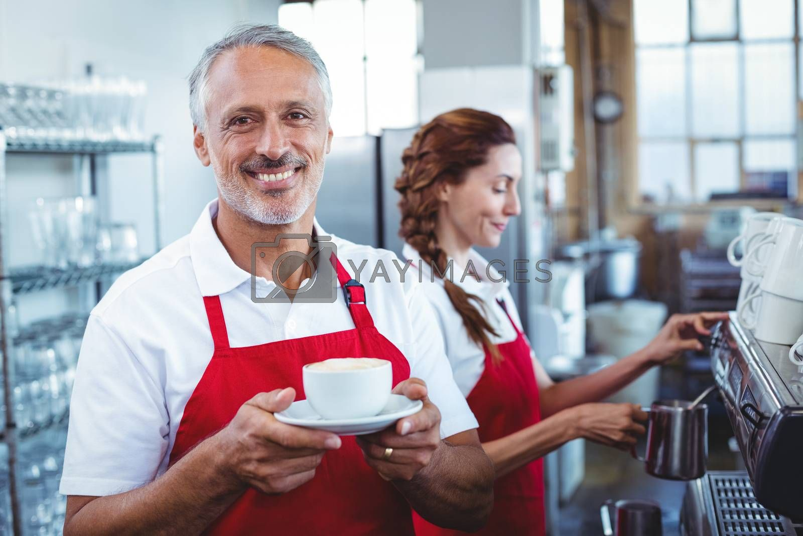 Royalty free image of Happy barista smiling at camera and holding a cup of coffee by Wavebreakmedia