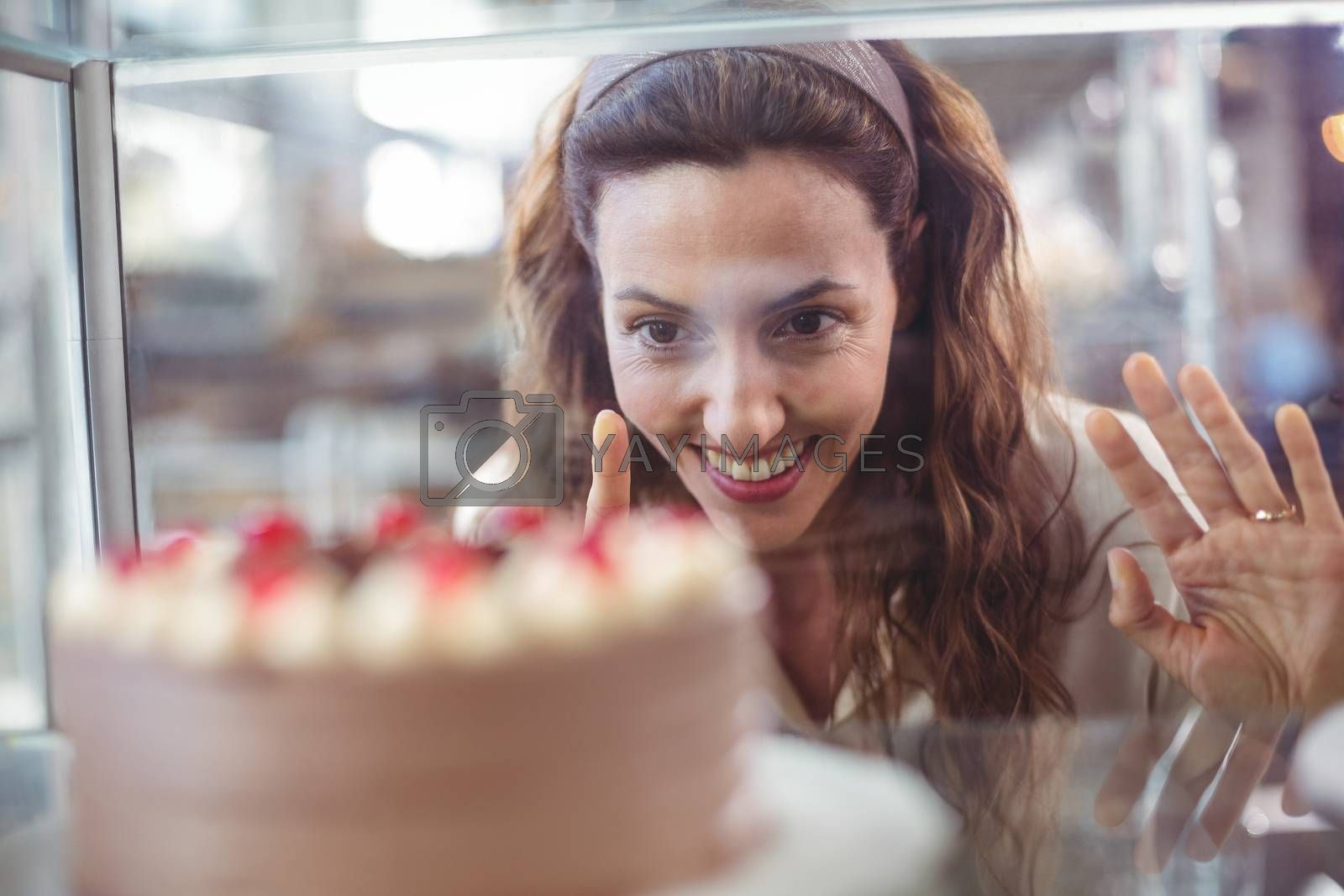 Royalty free image of Pretty brunette looking at chocolate cake through the glass by Wavebreakmedia