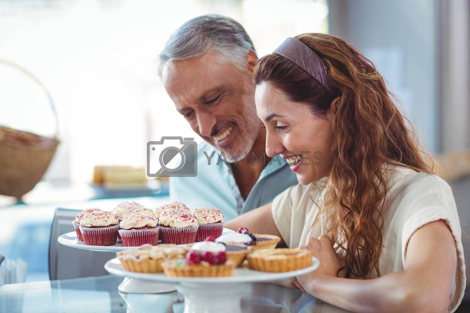 Royalty free image of Happy couple looking at pastries  by Wavebreakmedia