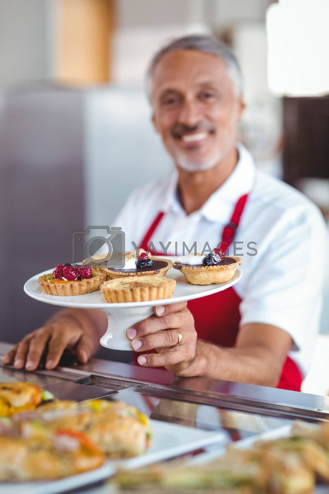 Royalty free image of Barista holding a plate of pastries by Wavebreakmedia