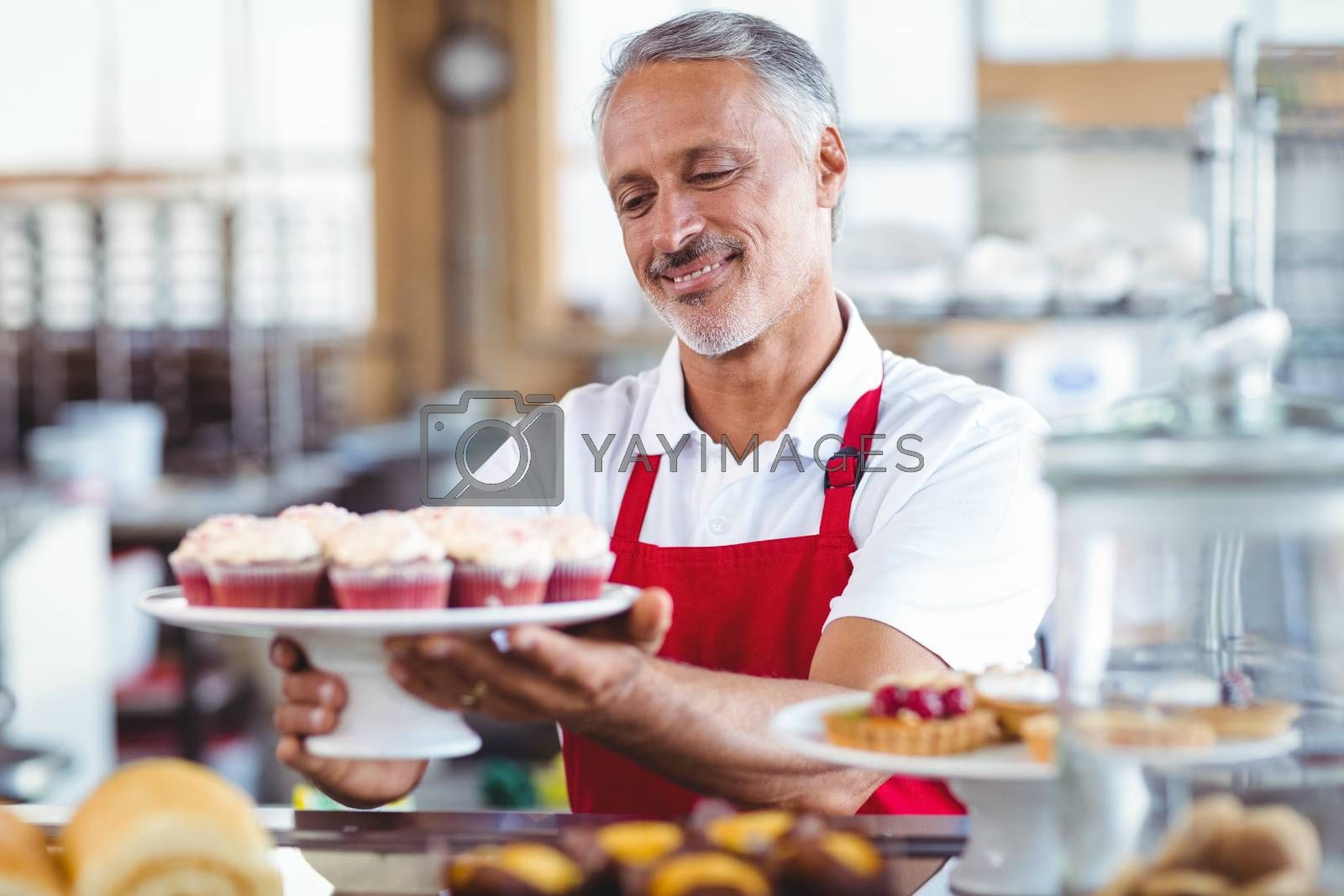 Royalty free image of Happy barista holding a plate of cupcakes by Wavebreakmedia