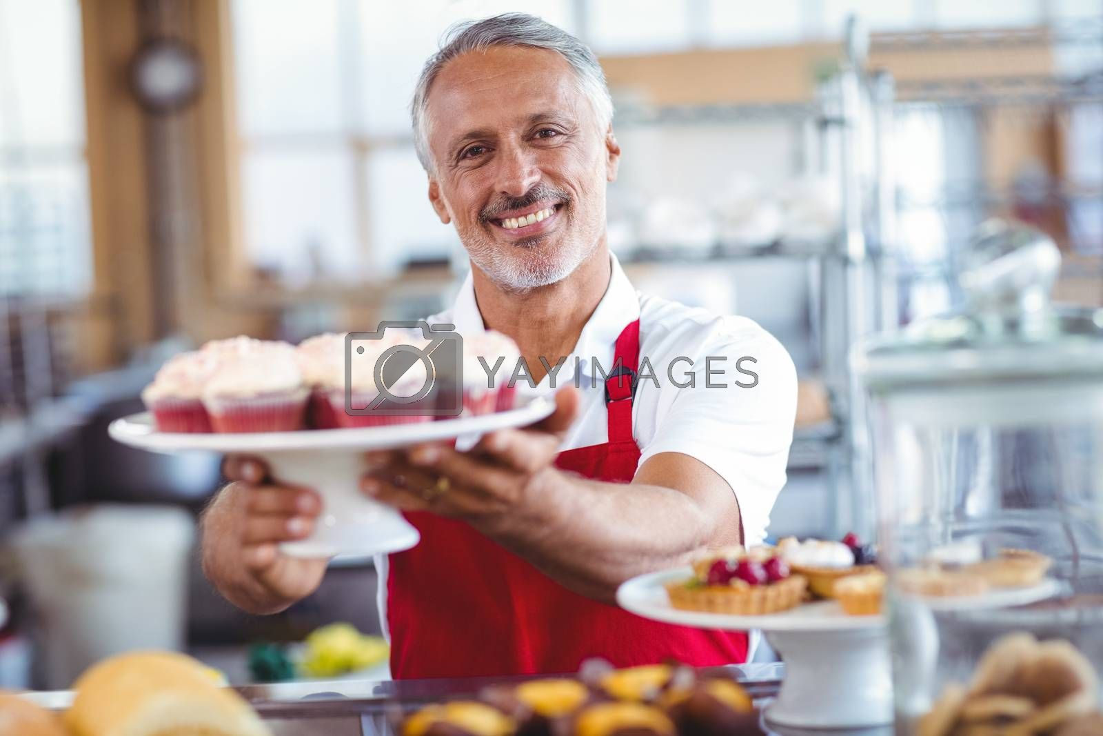 Royalty free image of Happy barista smiling at camera and holding a plate of cupcakes by Wavebreakmedia