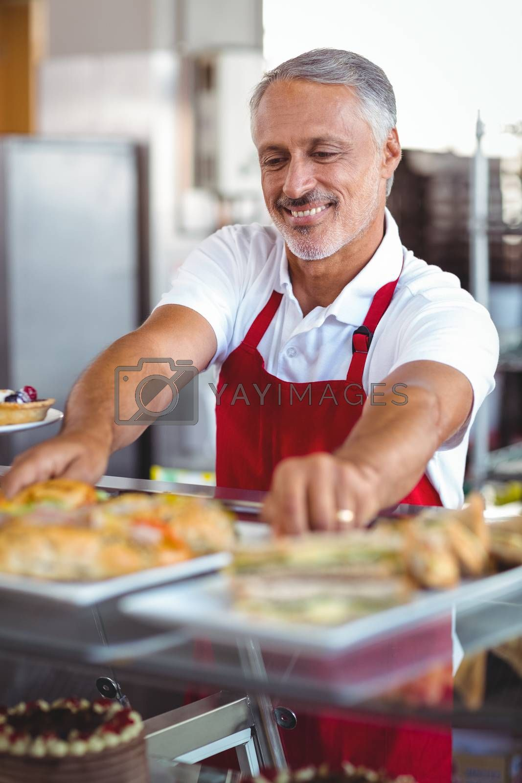Royalty free image of Barista putting plates of pastries on counter by Wavebreakmedia
