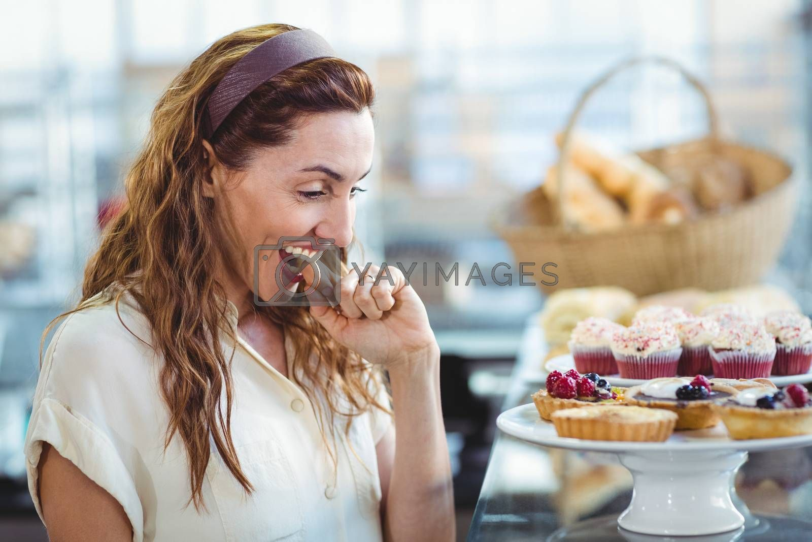 Royalty free image of Astonished pretty woman looking at cakes by Wavebreakmedia