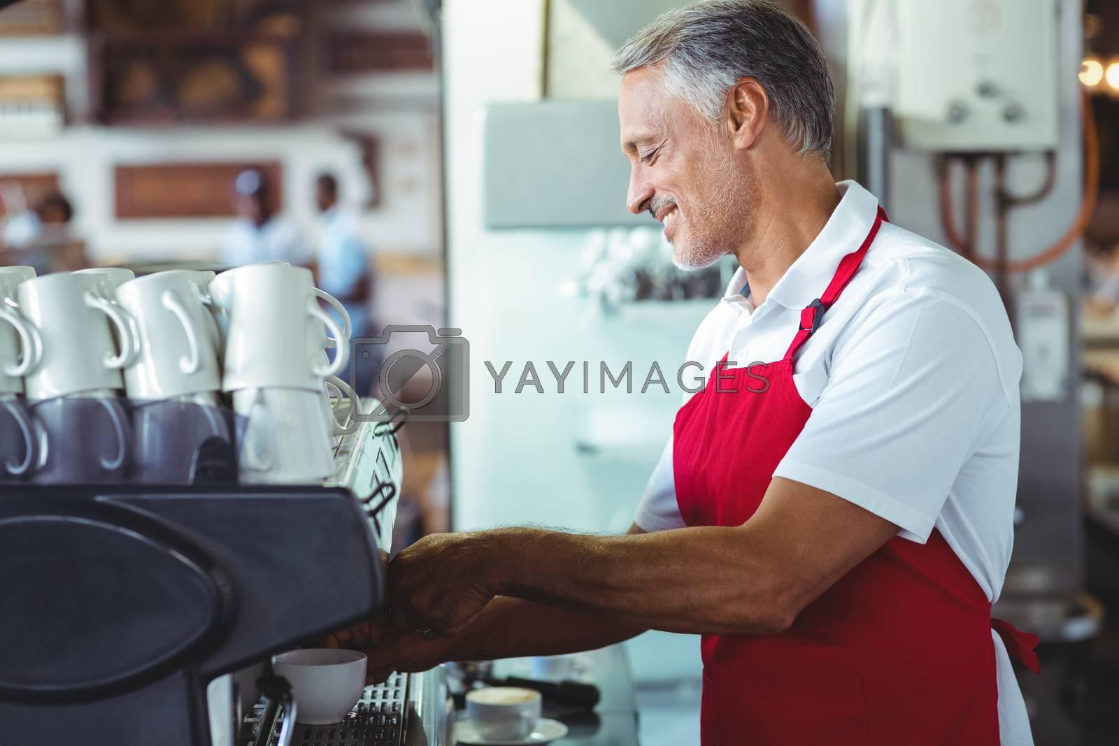 Royalty free image of Happy barista using the coffee machine by Wavebreakmedia