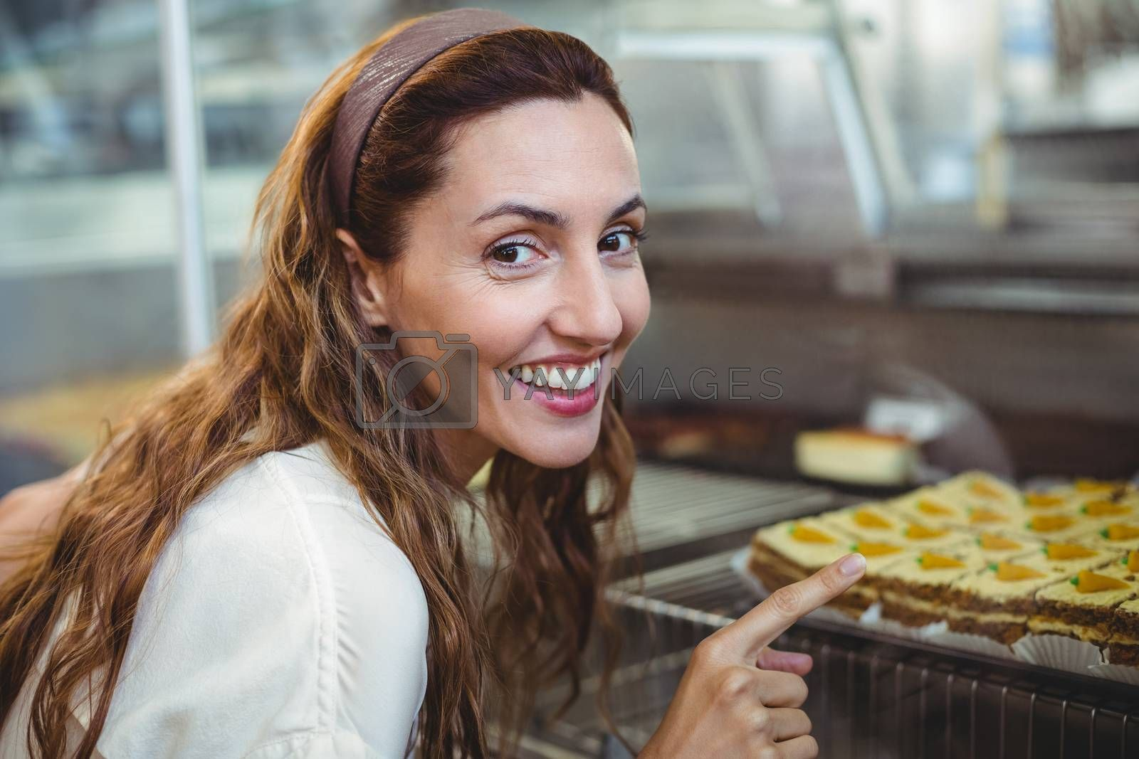 Royalty free image of Pretty brunette pointing at pastries through the glass by Wavebreakmedia
