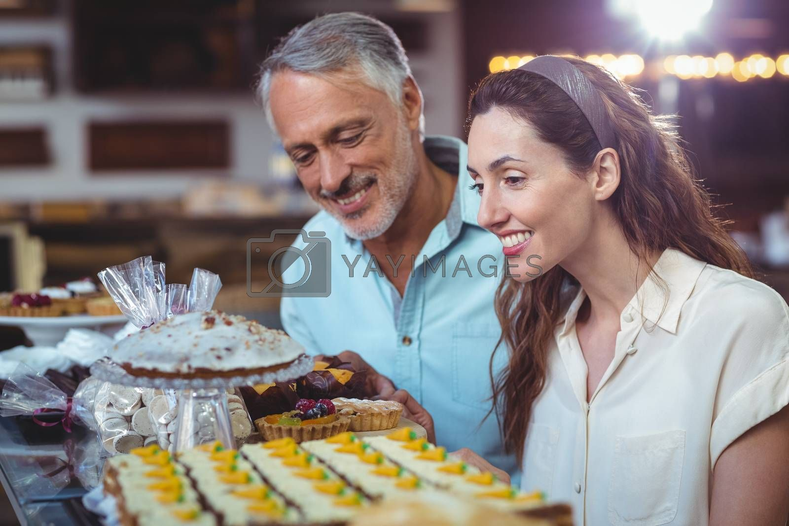 Royalty free image of Cute couple looking at cakes by Wavebreakmedia