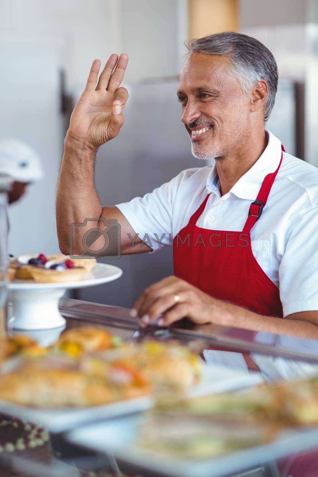 Royalty free image of Happy barista gesturing ok sign behind counter by Wavebreakmedia