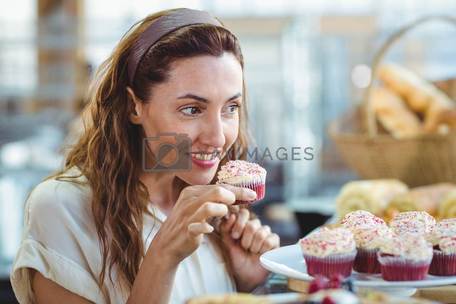 Royalty free image of Pretty brunette holding and smelling cupcake by Wavebreakmedia