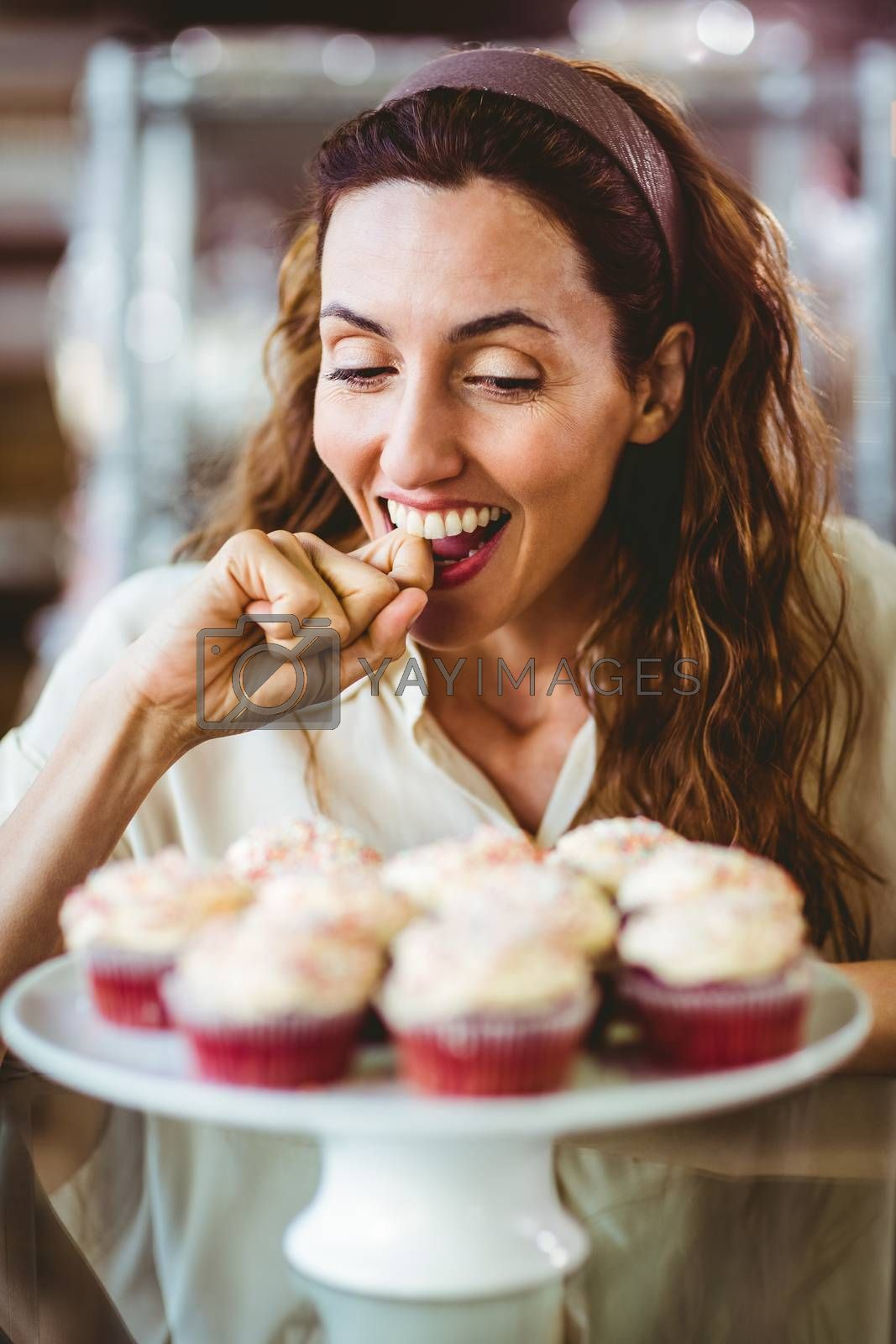 Royalty free image of Pretty brunette looking at cakes by Wavebreakmedia