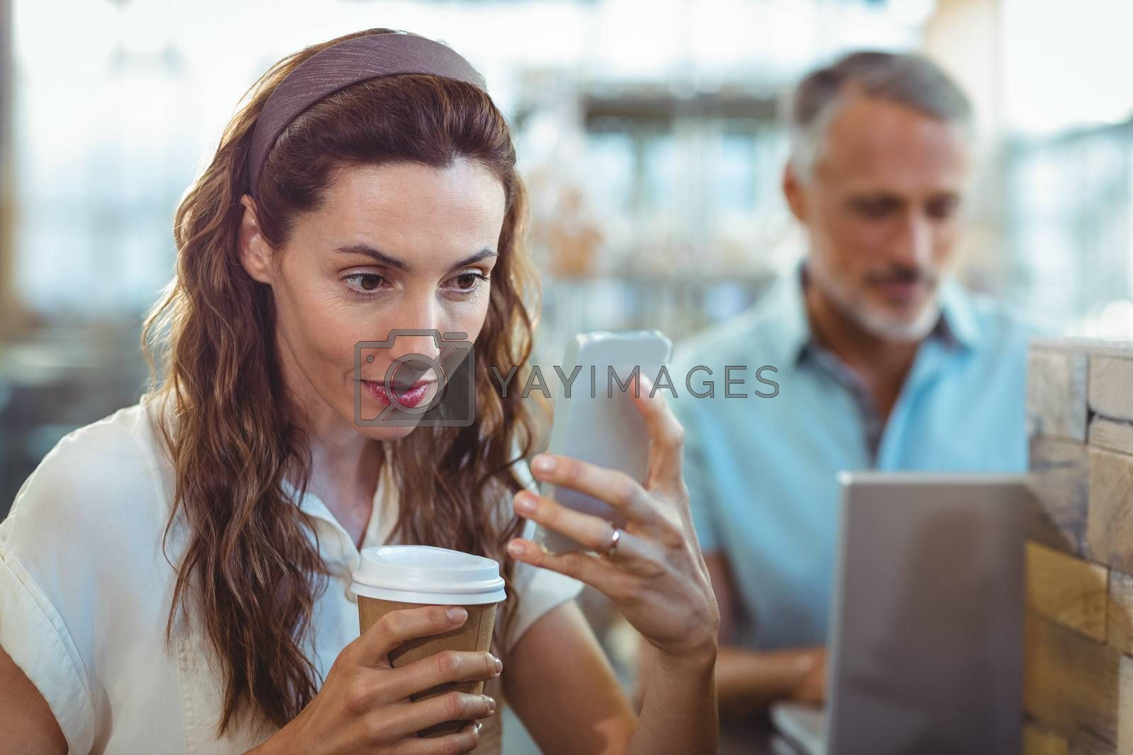 Royalty free image of Pretty brunette using her smartphone with coffee in her hand by Wavebreakmedia