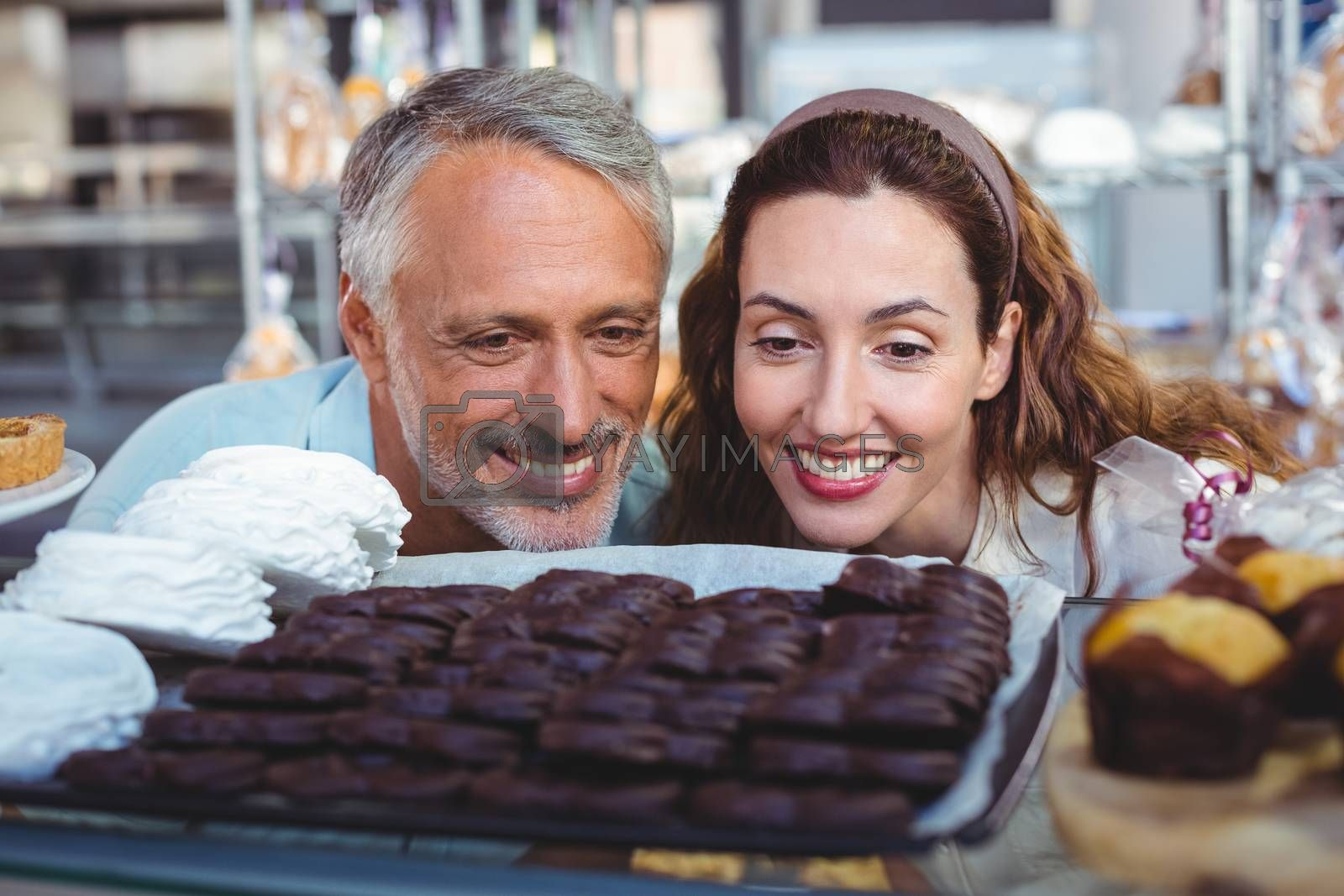 Royalty free image of Happy couple looking at cakes by Wavebreakmedia