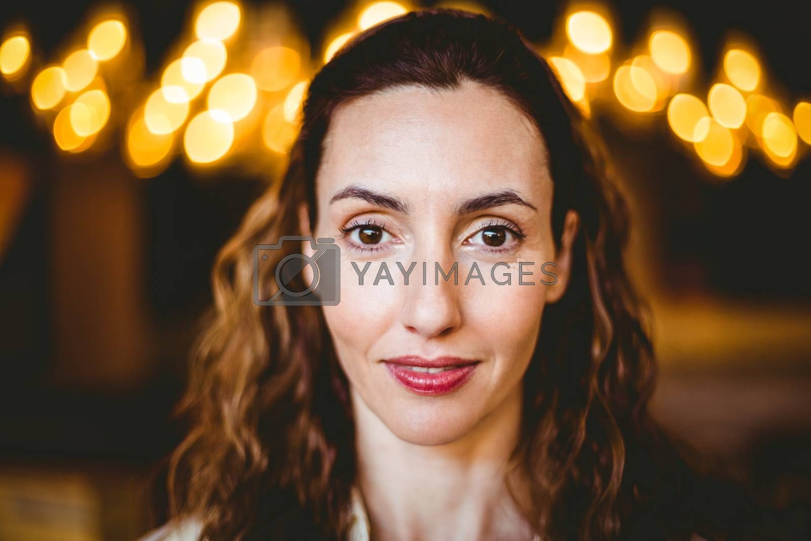 Royalty free image of Close up of calm brunette looking at camera by Wavebreakmedia