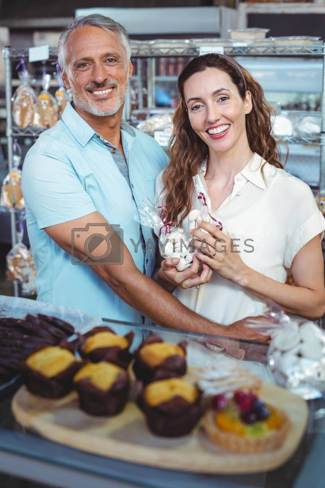Royalty free image of Cute couple looking at camera and standing arm around by Wavebreakmedia