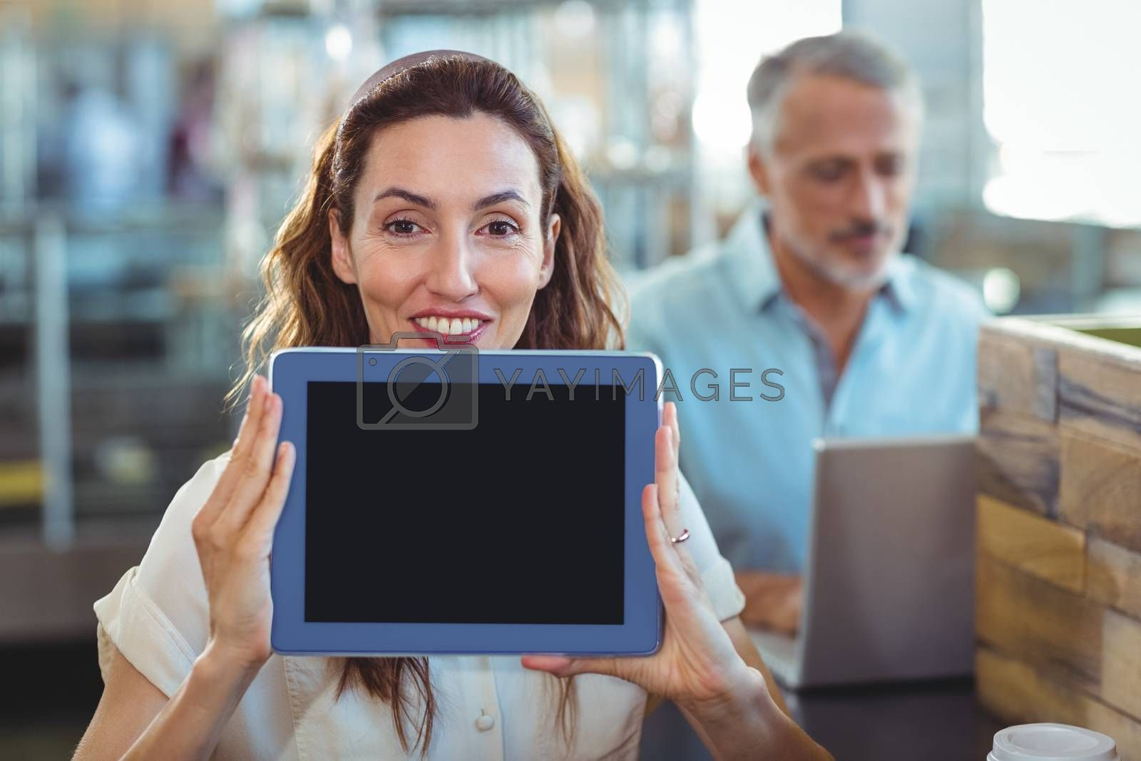Royalty free image of Pretty brunette looking at camera and showing tablet by Wavebreakmedia