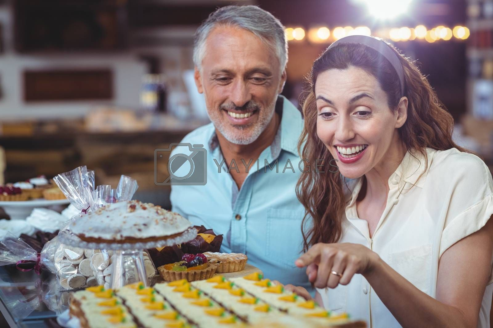 Royalty free image of Happy couple pointing pastries by Wavebreakmedia