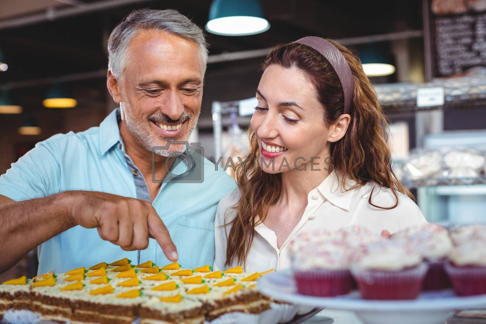 Royalty free image of Cute couple pointing pastries by Wavebreakmedia