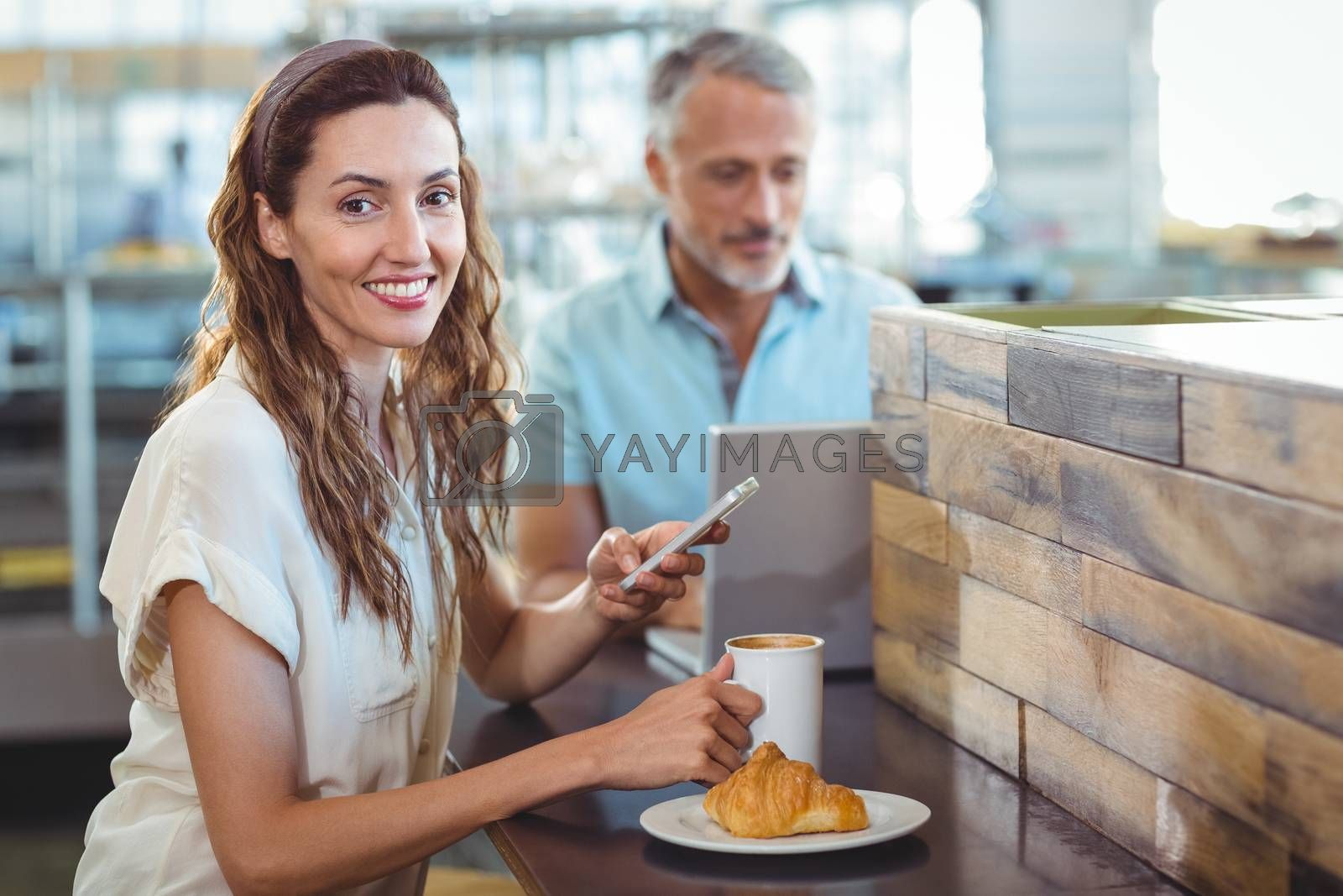 Royalty free image of Pretty brunette smiling at camera and using her smartphone by Wavebreakmedia