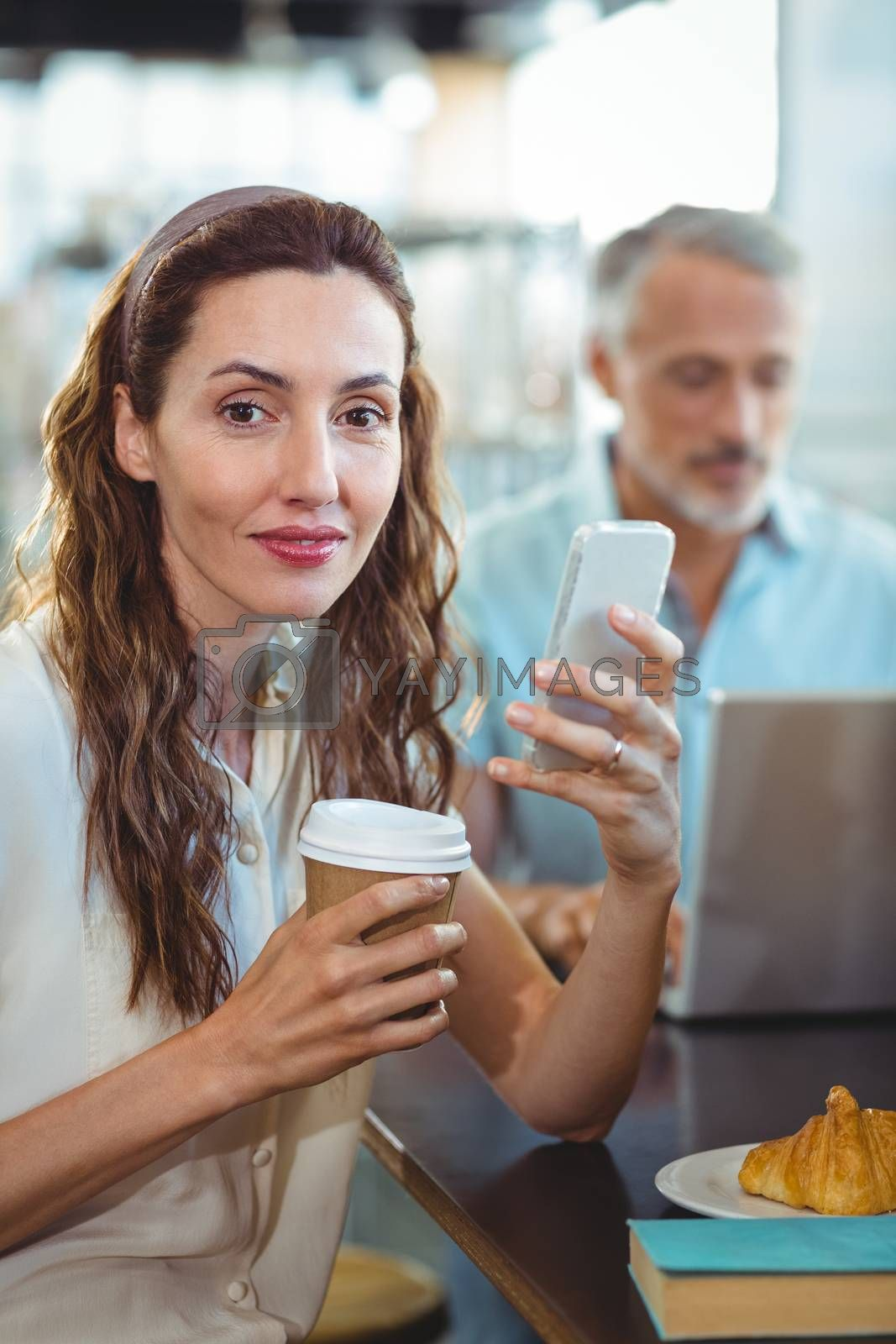 Royalty free image of Pretty brunette looking at camera with smartphone and coffee in her hands by Wavebreakmedia