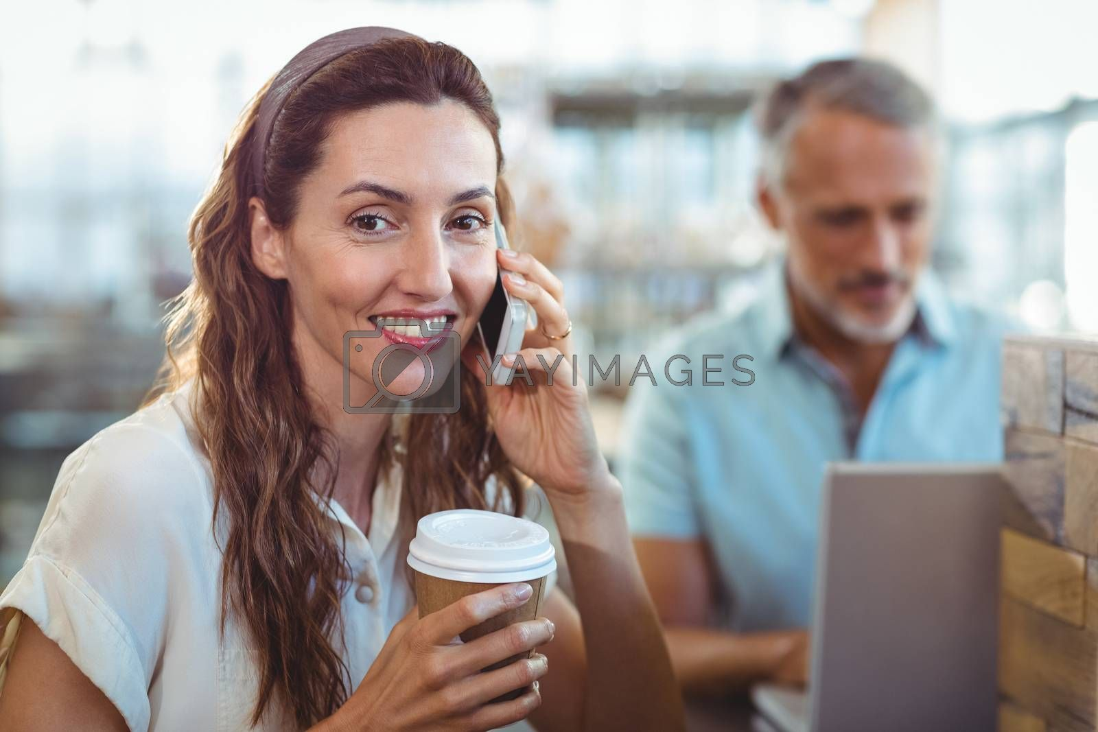 Royalty free image of Pretty brunette smiling at camera and having phone call by Wavebreakmedia