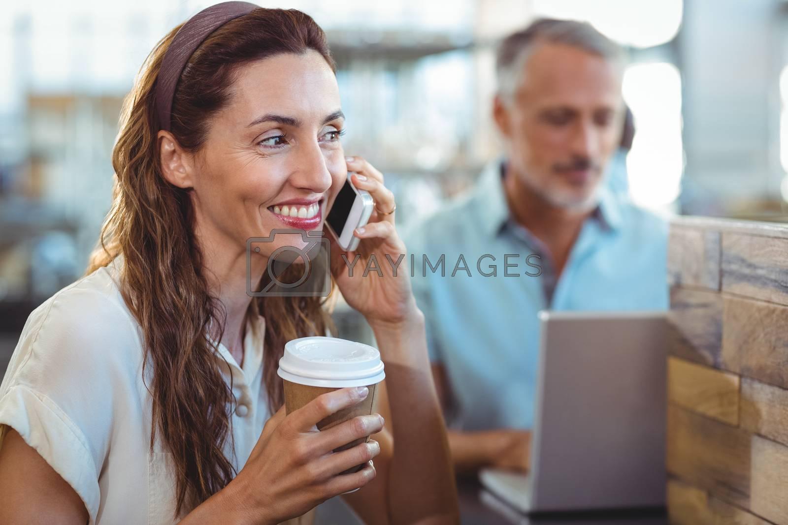 Royalty free image of Pretty brunette having phone call by Wavebreakmedia