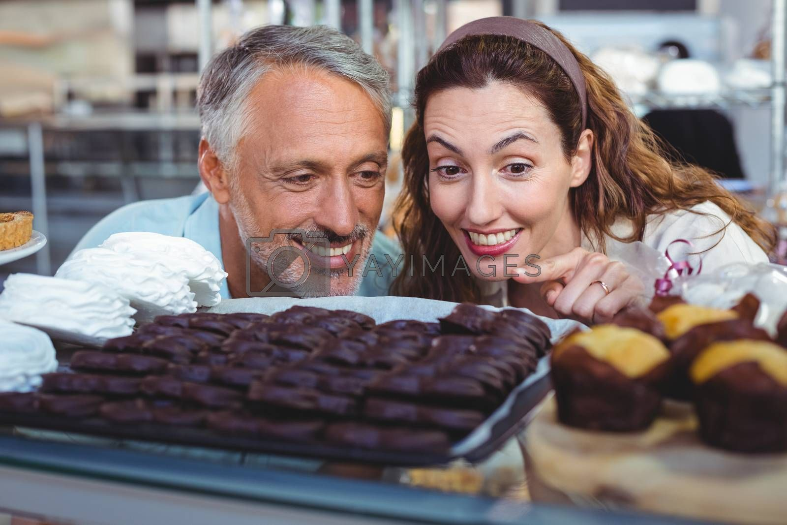 Royalty free image of Happy couple pointing cakes by Wavebreakmedia