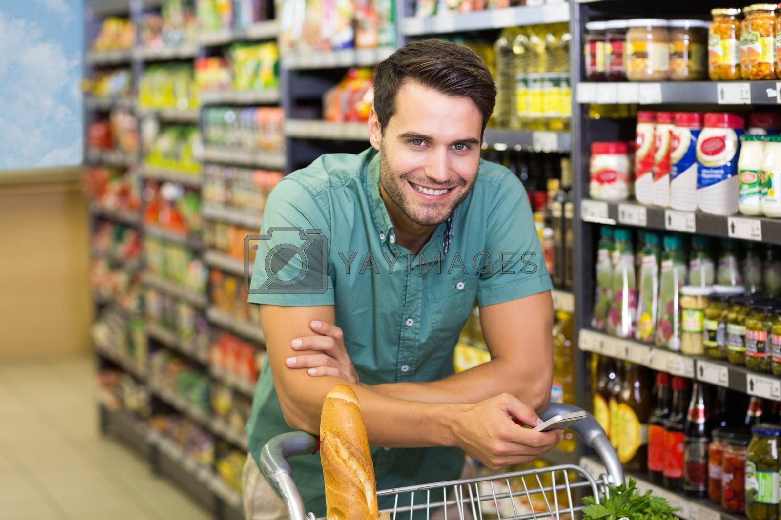Royalty free image of Portrait of smiling man buy food and using his smartphone  by Wavebreakmedia