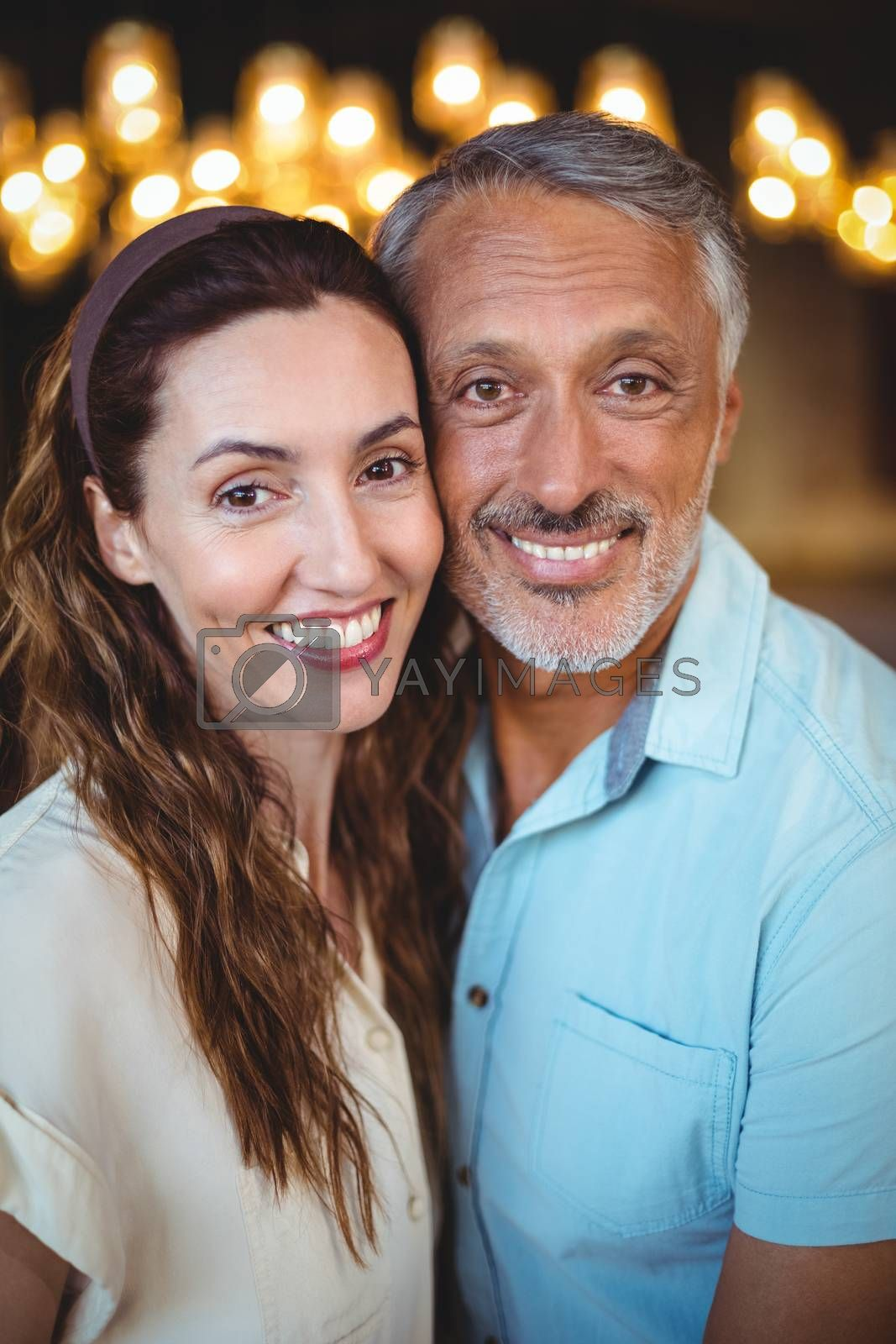 Royalty free image of Portrait of happy couple smiling at camera by Wavebreakmedia