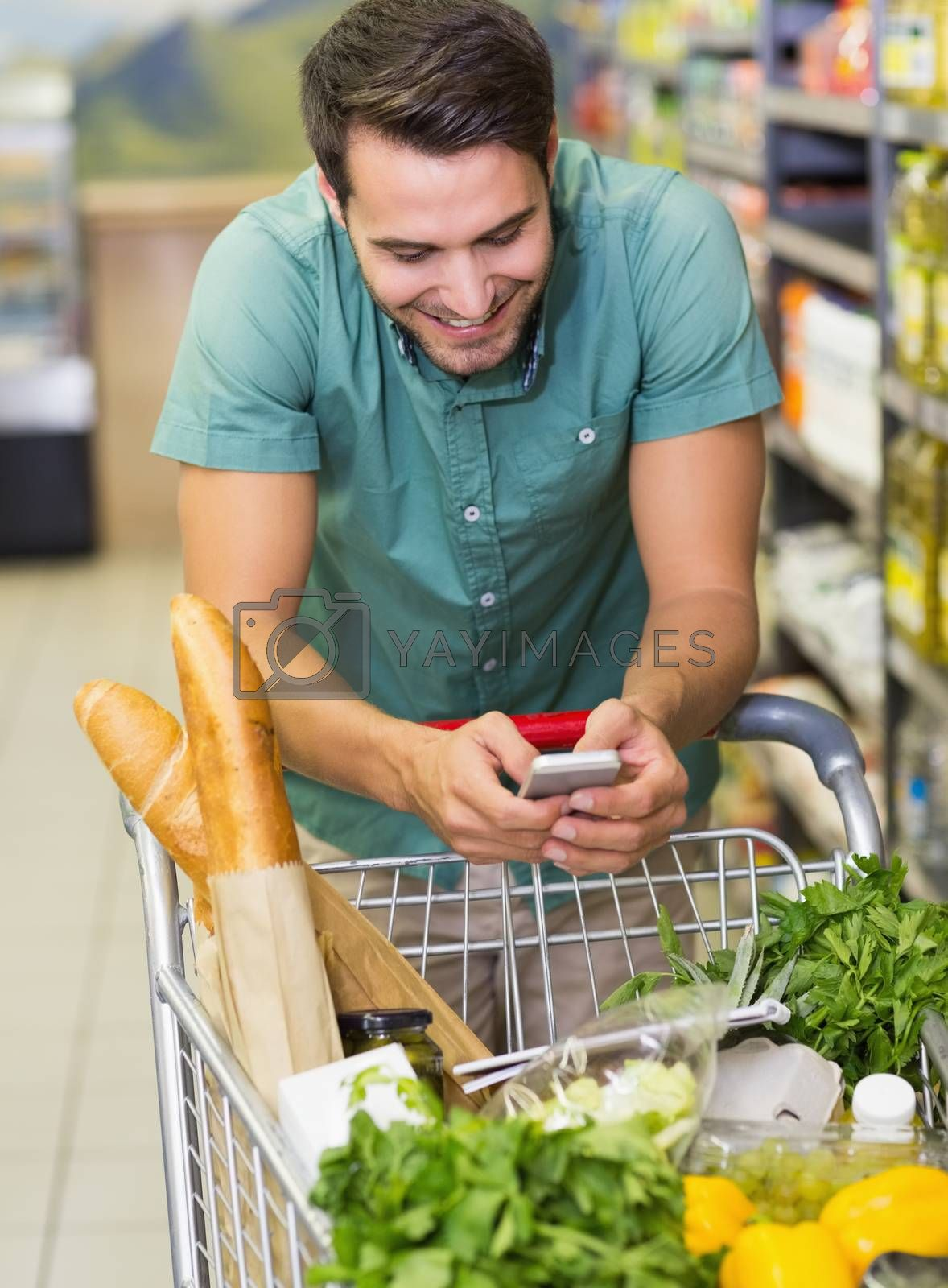 Royalty free image of Smiling man buy products and using his smaprtphone  by Wavebreakmedia