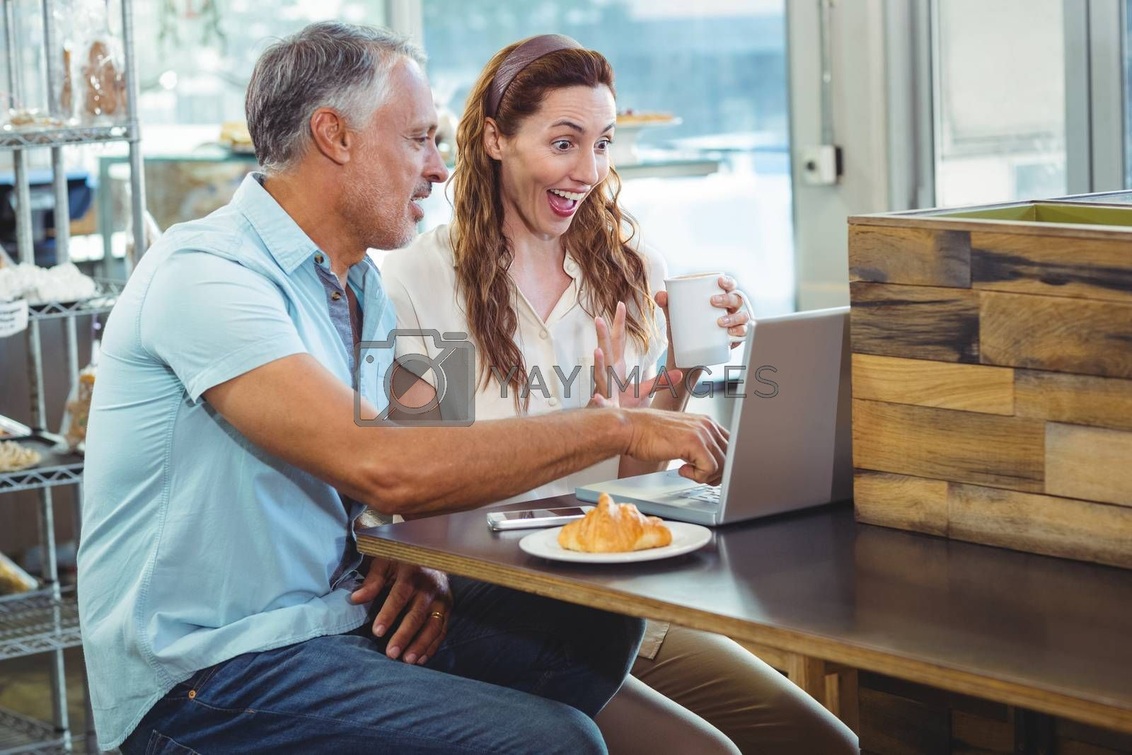 Royalty free image of Happy couple watching something funny on laptop by Wavebreakmedia