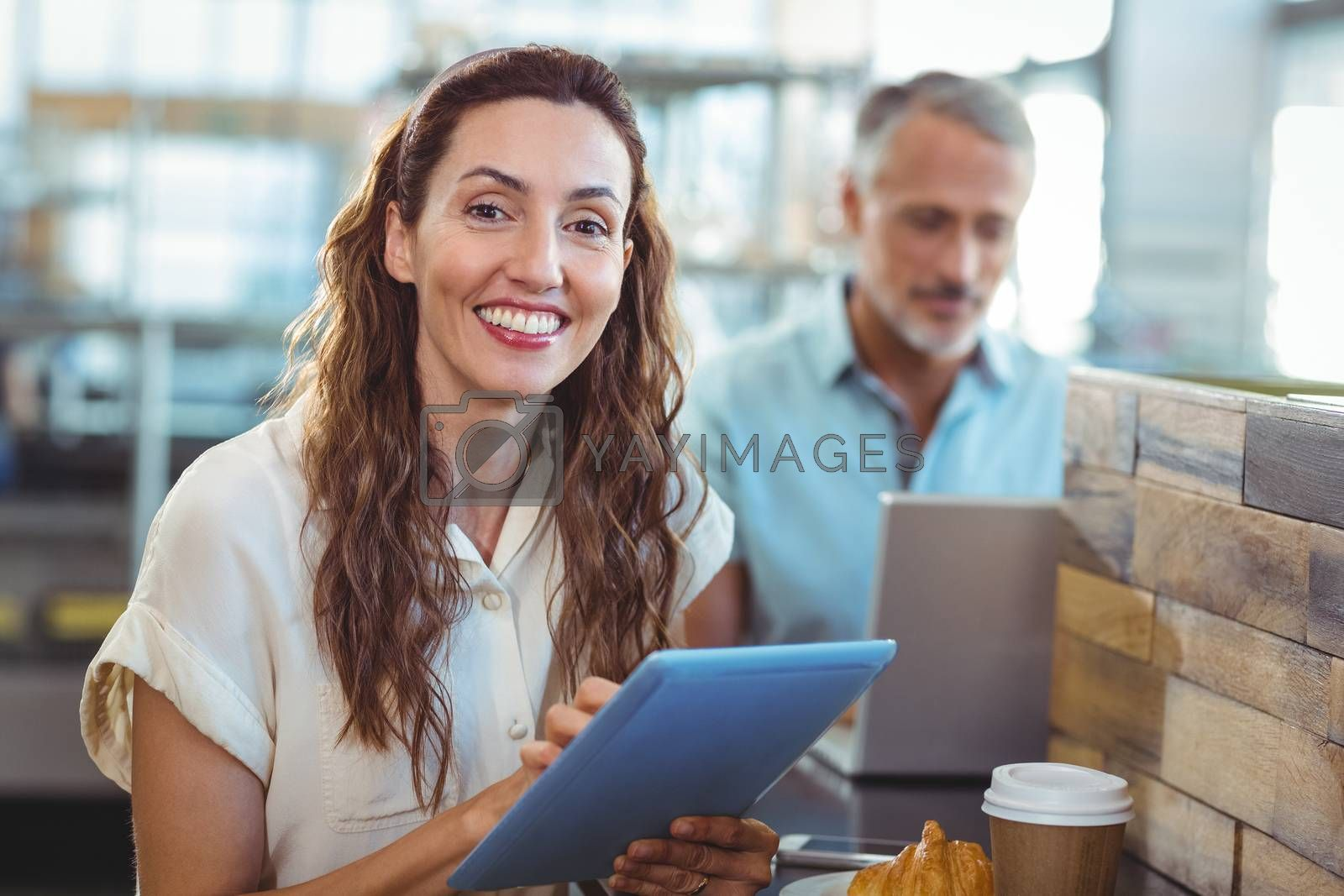 Royalty free image of Pretty brunette smiling at camera and using tablet by Wavebreakmedia