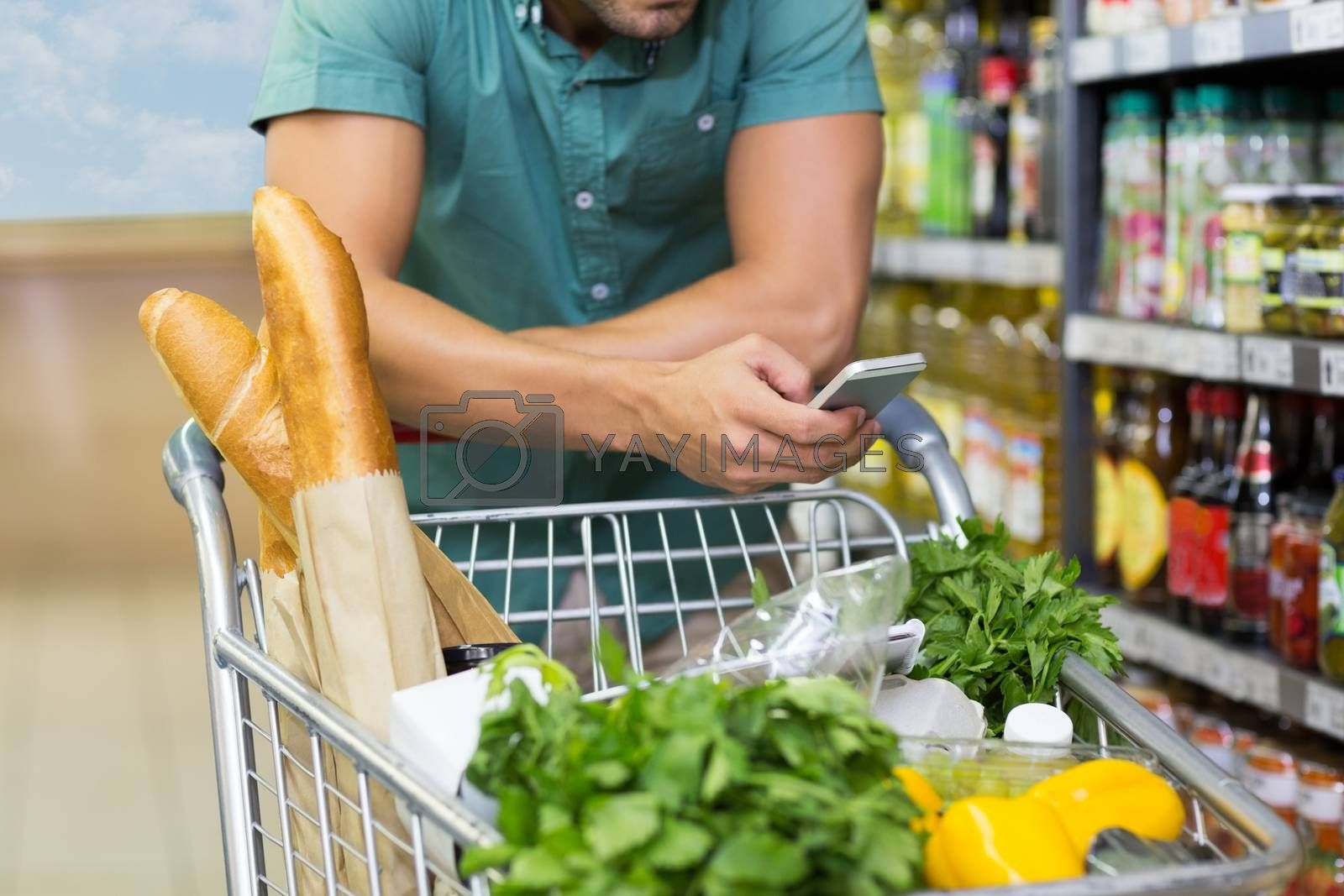 Royalty free image of Man buy products and using his smartphone  by Wavebreakmedia