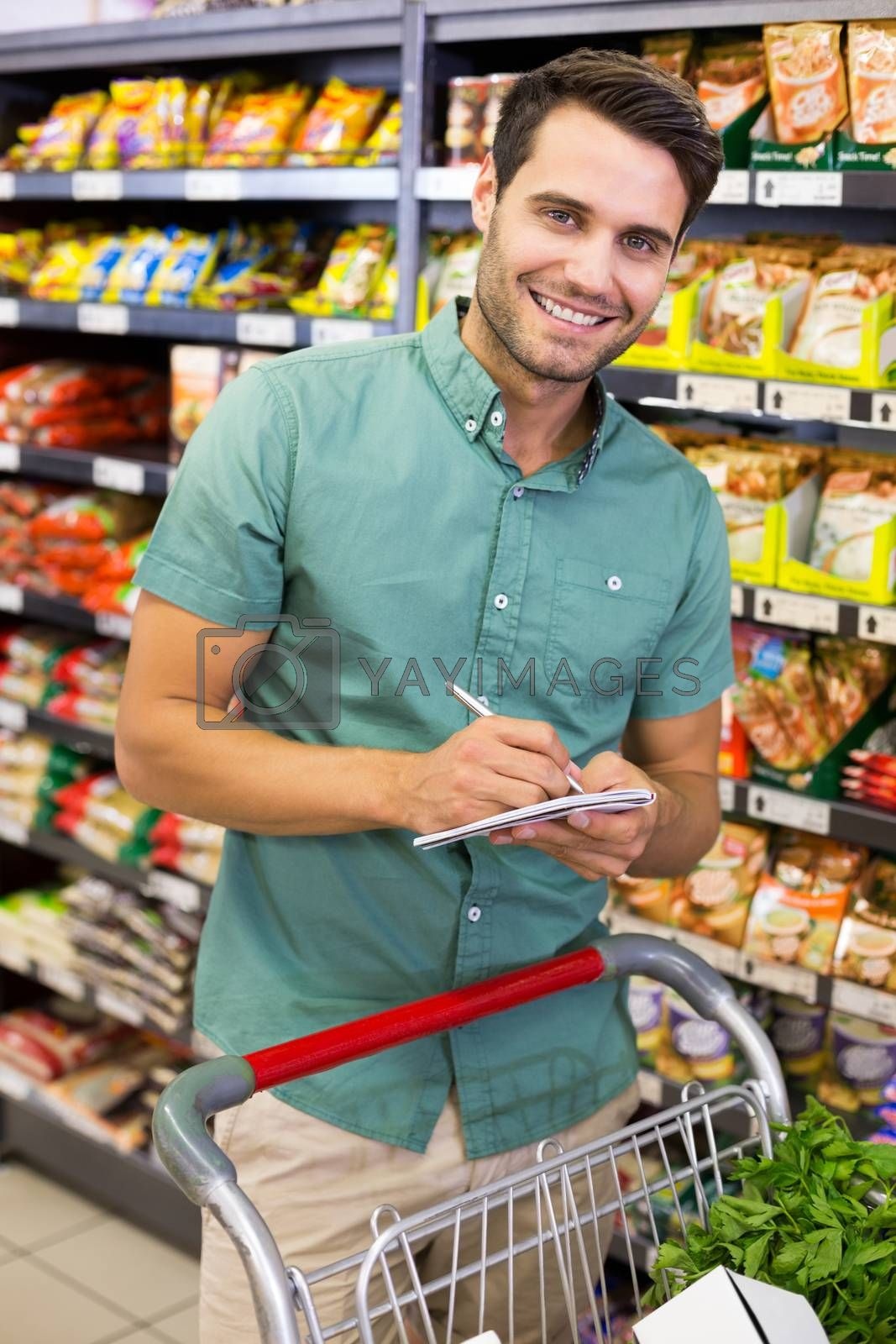 Royalty free image of Portrait of smiling man writing on his notepad in aisle  by Wavebreakmedia