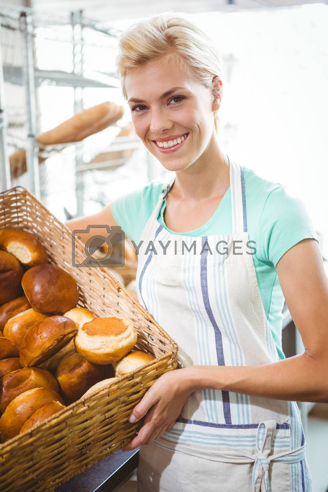 Royalty free image of Smiling waitress carrying basket of bread by Wavebreakmedia