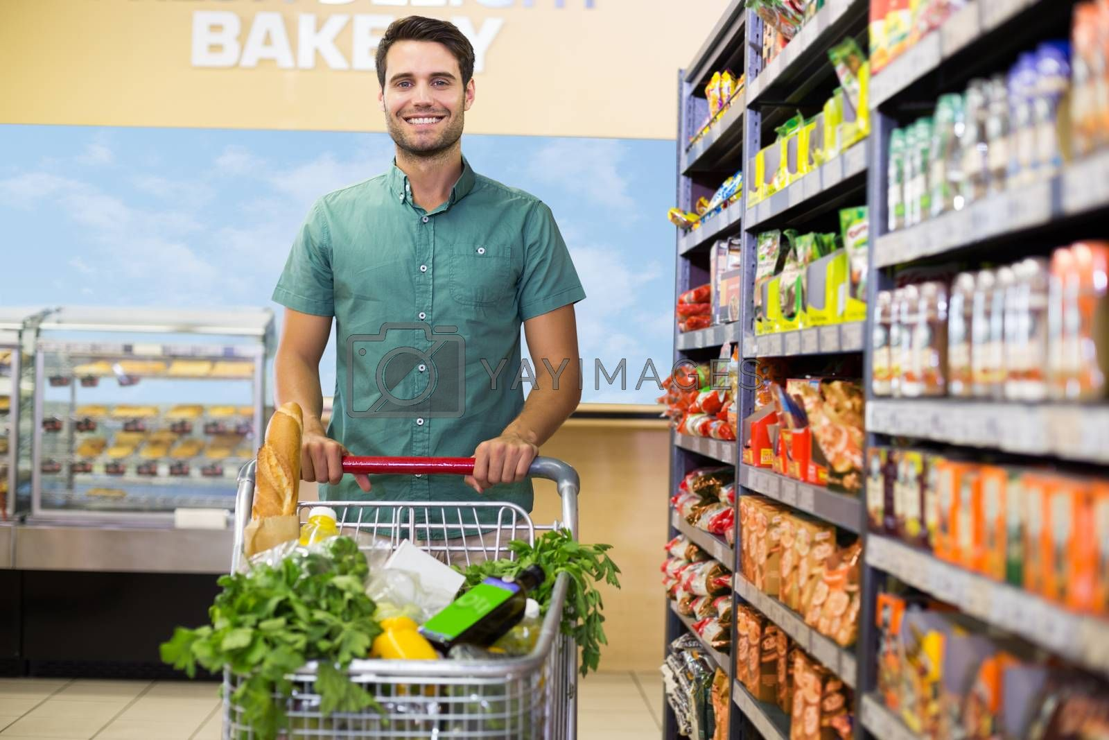 Royalty free image of Portrait of smiling man walking with his trolley on aisle  by Wavebreakmedia