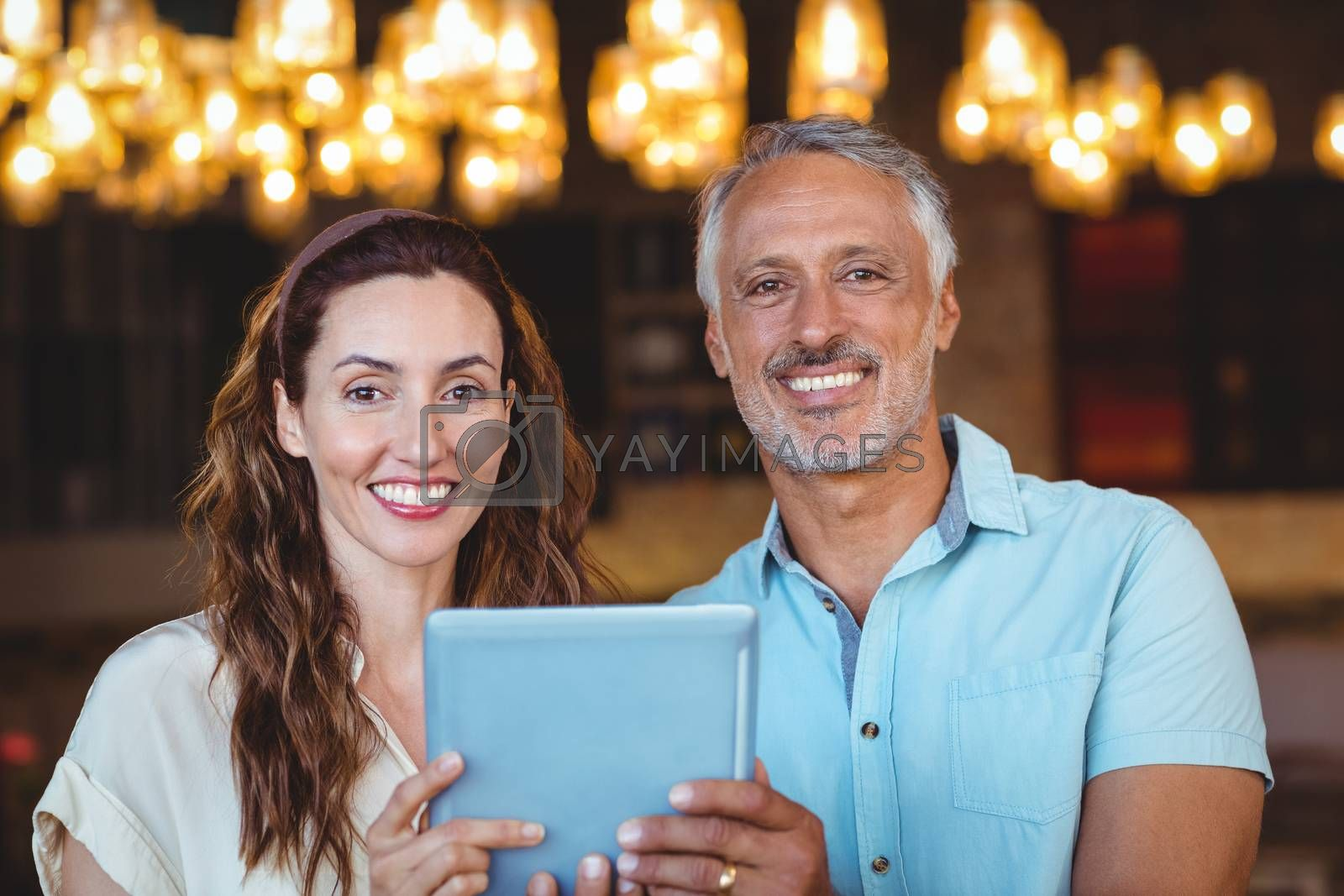 Royalty free image of Happy couple smiling at camera and using tablet by Wavebreakmedia