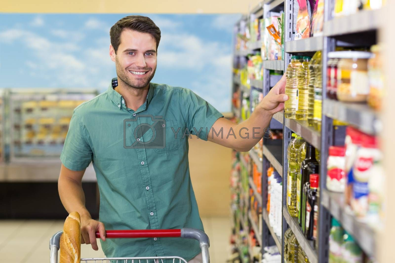 Royalty free image of Portrait of smiling man taking oil in the shelf of aisle  by Wavebreakmedia