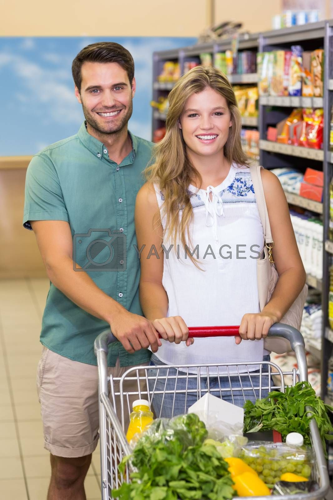 Royalty free image of Portrait of smiling bright couple buying products  by Wavebreakmedia