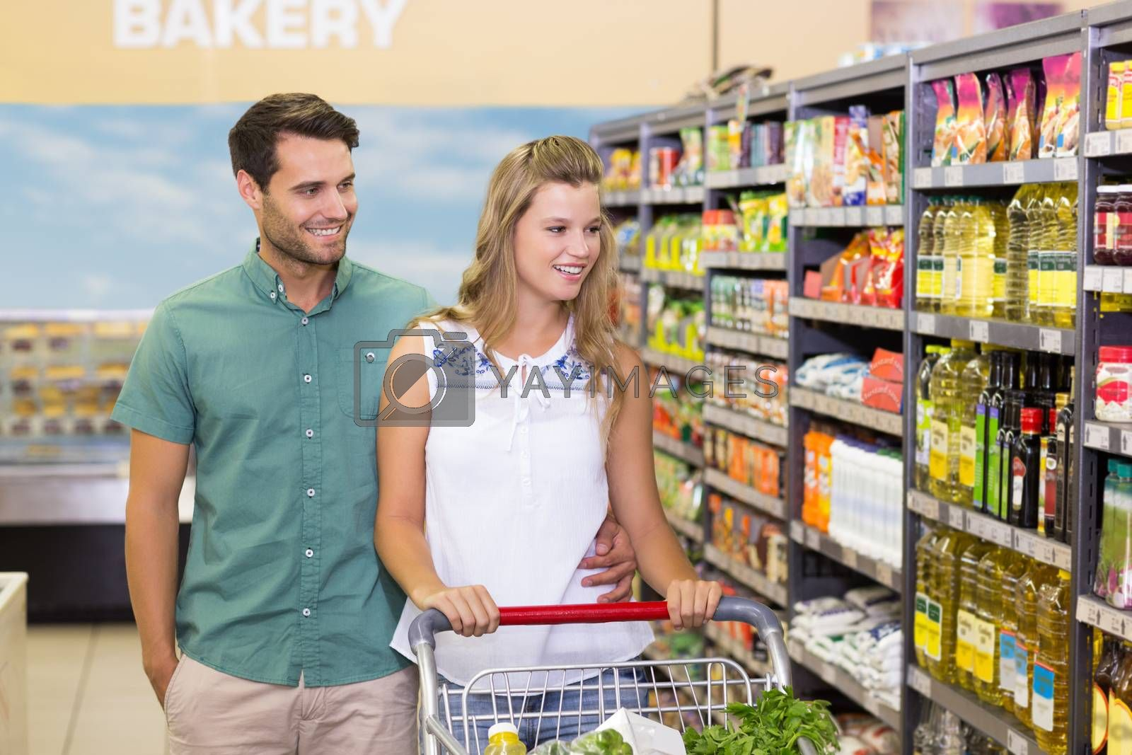 Royalty free image of Bright couple buying products in aisle  by Wavebreakmedia
