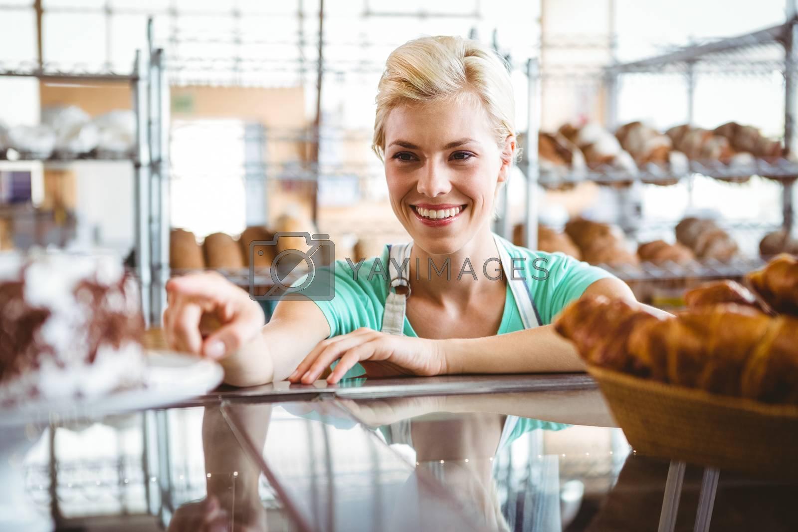Royalty free image of Smiling waitress posing next basket of bread by Wavebreakmedia
